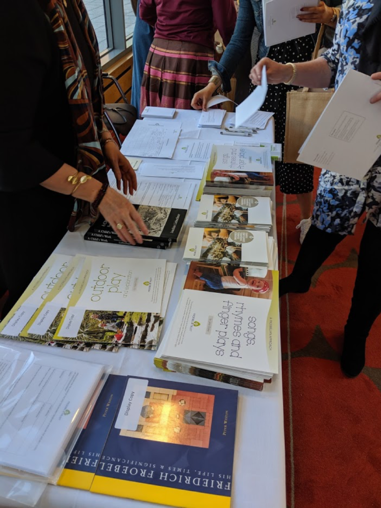 Froebel Trust pamphlets, e.g. about outdoor play and songs, rhymes and games, are displayed on a table surrounded by conference-goers